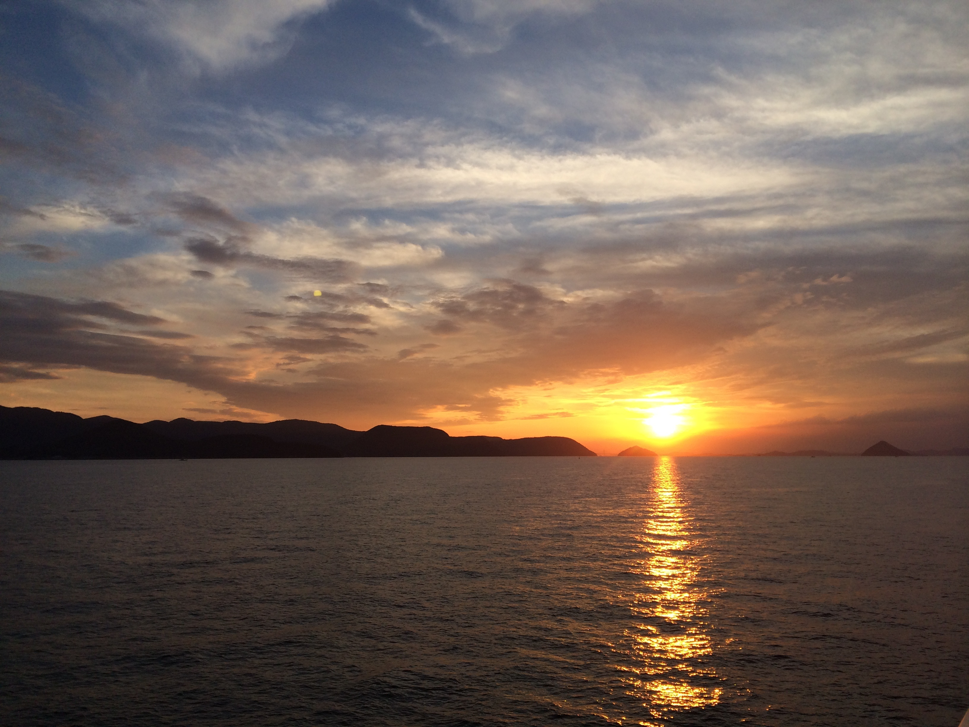 The summer sun sets over the Seto Inland Sea, taken from the ferry